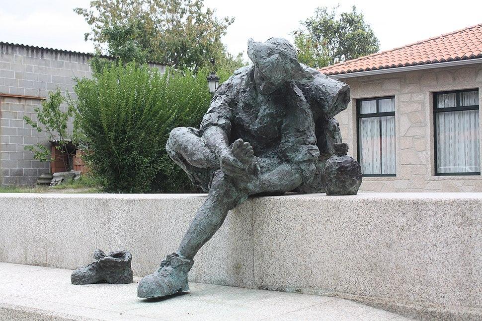 Estatua dun peregrino á porta do albergue do Pino.