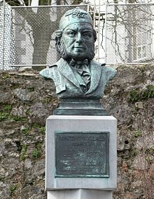 "An outdoor bust of a bearded man wearing a large patterned cap and a dicky bow tie. A plaque beneath reads: Vincent Wallace composer. Born Waterford 1812, died Pyrenees 1865. ""In happy moments day by day, The sands of life may pass. In swift but tranquil tide away, From times inferring glass."""