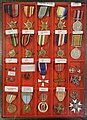 WW2 Military decorations medals British Norwegian French Patriotic pins Flags Haakon 7 Krigskorset etc Lofoten krigsminnemuseum Norway DSC00140 Cropped Adjusted perspective.jpg