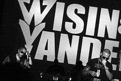 Wisin & Yandel, performing in front of a large sign with their names