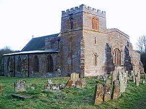 A stone church seen from the northwest with a squat tower in the foreground, with the north aisle to the left and the west end of the nave to the right