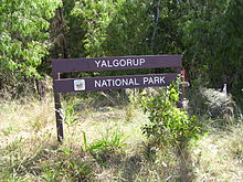 Wooden sign in front of trees and vegetation