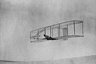 Wright Glider -  The 1902 Wright Glider (Wilbur piloting) on one of its early test flights before replacement of the fixed double rear vertical rudder with a single steerable rudder