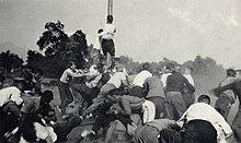 Noin kolmenkymmenen miehen ryhmä taistelee rähinää vastaan, joista osa on maassa ja yksi onnistuu kiipeämään keskelle suurta puupylvästä.