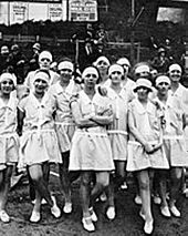 black and white photo of a group of women wearing light coloured dresses, with hair bands in their hair