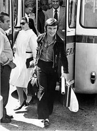 A black and white picture stepping out of a bus with briefcases in his hands.