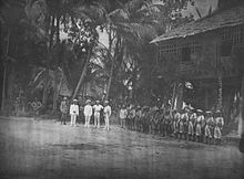 A line of soldiers in tropical uniforms stand in front of a hut in a jungle clearing. In front of them stand a group of five men facing towards the camera.