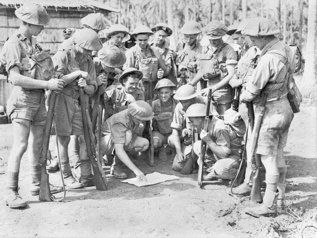 Soldiers in tropical uniforms stand around a map prior to a patrol