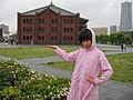A girl sets a pose in front of red brick warehouse, Red Brick Park, Kanagawa, Japan; May 2011.jpg
