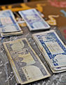 Afghanis, or Afghan currency, are arranged on the desk of the Shah Joy district chief of police to pay members of the Afghan Local Police (ALP) at the Shah Joy district center in Zabul province, Afghanistan 120201-N-CI175-108.jpg