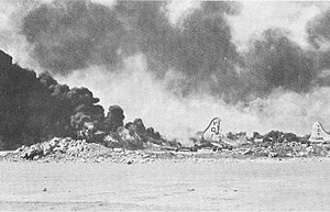 Black and white photograph depicting an aircraft on fire. The tail of another aircraft is visible at the right of the photo and there is a large amount of smoke in the air.