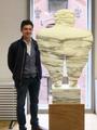 Albin Saelens poseert naast een marmeren beeld van Kobe (La Baigneuse - 1995 - Bianco Carrara Fantastico - 134 x 85 x 10 cm) in The Phoebus Foundation.png