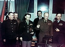 Six smiling and laughing men and one woman in uniform. Eisenhower is brandishing a pen.