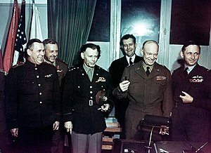 Group shot of six smiling men (and one barely visible woman), each in a different military uniform, standing behind a writing desk. Eisenhower is holding three fountain pens. In the background are flags, including the US flag.