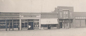 Ambia, Indiana - Ambia, Store Front with the Post Office, Old Harness Shop, Barber Shop, and Millinery Shop, circa 1920