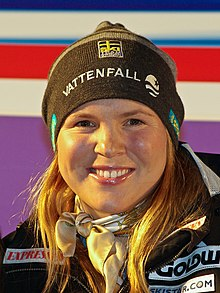 Anja Parson, close in on her face, as she smiles.  She is wearing a black ski hat.