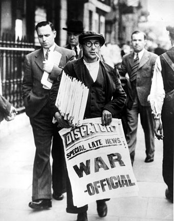 Newspaper vendor holding stack of newspapers and sign announcing the state of war Announcing state of war with Germany cph.3c32594.jpg
