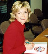 A colour photograph of a woman with blonde hair and blue eyes wearing a red dress shirt, writing in a book, and smiling at the viewer
