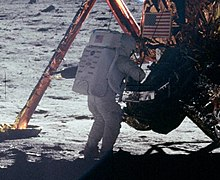 A grainy picture from behind of a human figure in white space suit and backpack standing in front of the Lunar Module on the surface of the Moon. A landing leg is visible and the U.S. flag on the descent stage.