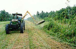 Asajaya District - Cutting grass using tractor with side trimmer at Asajaya Drainage Project.