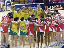 Two teams of female netballers standing in a large circle with their arms around each other