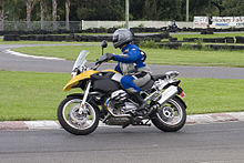 Black and yellow BMW R1200GS motorcycle, being ridden around a corner on a race track by a rider in a blue and grey suit