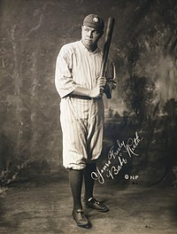 A black-and-white photo of a man posting in front of the camera. He is wearing his uniform, holding a baseball bat. He is posing for the camera but looking away slightly from it. An autograph of the subject is also seen in the middle of the picture.