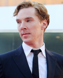 Benedict Cumberbatch facing left with blonde hair wearing a suit and tie