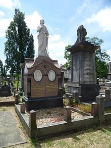 An elaborate funerary monument of red granite, with two white marble tondi of Blondin and his wife, surmounted by a marble statue of a female figure clad in robes holding an anchor