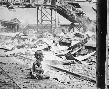 Black-and-white photograph of a baby crying on a platform of Shanghai's South Station after aerial bombing by Japanese forces, their clothes burned and their skin sooty, with flaming wreckage in the background