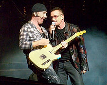 The Edge and Bono stand on a darkened stage, with lit-up smoke behind them. The Edge is strumming a guitar while Bono holds a microphone to his mouth.