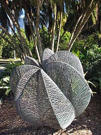 a copper sculpture comprising seven segments wrought out of undulating copper wire, standing beneath a cluster of palm trees