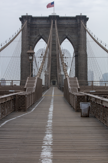The Brooklyn Bridge's elevated promenade with the pedestrians on the right and cyclists on the left.