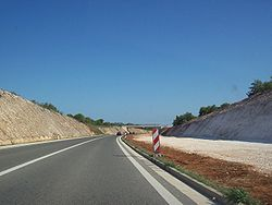 A completed two-lane carriageway and earthworks completed for a parallel carriageway