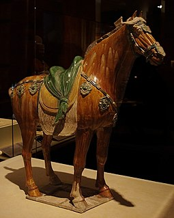 Tomb figure of a horse with a carefully sculpted saddle, decorated with leather straps and ornamental fastenings featuring eight-petalled flowers and apricot leaves. CMOC Treasures of Ancient China exhibit - pottery horse, detail 1.jpg