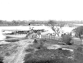 Passengers leaving the Silver Star river steamer ferry at Coffee Point (site of the South of Perth Yacht Club), with the old Canning Bridge in the background. ca. 1906.