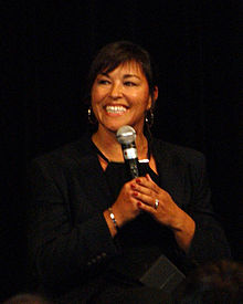 A woman with short black hair smiles as she speaks into a microphone. She is wearing a black blouse and coat.