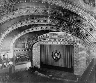 Proscenium - The proscenium arch of the theatre in the Auditorium Building, Chicago. The proscenium arch is the frame decorated with square tiles that forms the vertical rectangle separating the stage (mostly behind the lowered curtain) from the auditorium (the area with seats).