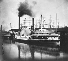 Black-and-white photo of a pair of steamboats moored at a dock; smoke is issuing from one of the boat's funnels; the masts of several sailing ships are visible in the background