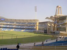 Back view of the entrance and a stand of a cricket stadium. Some people can be seen near the seats.