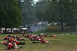 An open grassy area is strewn with bodies, most of them in red and white uniforms, although some with blue coats are visible farther back. In the distance there are white tents and a crowd of people, and a small thin cloud of smoke obscures the view a little.
