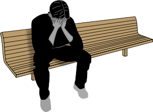 A depressed man sitting on a bench