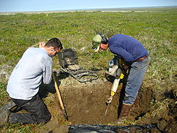 While these two men dig in Alaska to study soil, the hard permafrost requires the use of a jackhammer