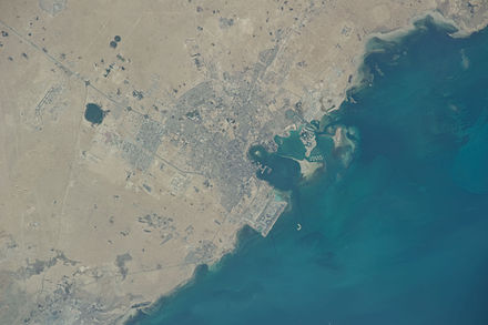 A satellite view of Doha on the East coast of Qatar. As with most world cities, Doha developed on the water front around the Souq Waqif area today. It gradually spread out in a radial pattern with the use of ring roads. Doha, Qatar Astronaut Imagery.JPG