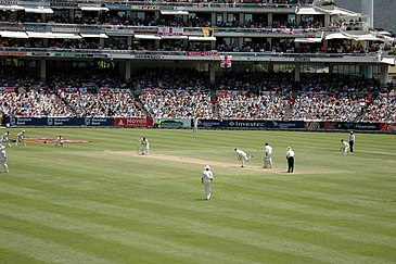 A Test match between South Africa and England in January 2005. The men wearing black trousers on the far right are the umpires. Test cricket is played in traditional white clothes and with red balls.