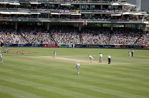 A Test match between South Africa and England in January 2005. The men wearing black trousers on the far right are the umpires. Teams in Test cricket, first-class cricket and club cricket wear traditional white uniforms and use red cricket balls, while professional limited overs teams usually wear multi-coloured uniforms and use white balls.