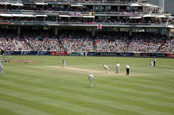 A Test match between South Africa and England in January 2005. The two men wearing black trousers are the umpires. Test cricket is played in traditional white clothes and usually with a red ball - a pink ball in full day/night Tests England vs South Africa.jpg