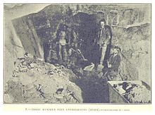 Inside a gold mine; men stand in a rough underground passage.