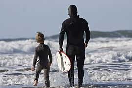 Un enfant et un homme en combinaison de natation marchant vers la mer