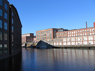 Tammerkoski - The north part of Tammerkoski. On the left, the former Finlayson textile mill. On the right, the former metal and textile factory Tampella. The Tampella powerstation is behind the large arched window. The powerstation inlet channel is visible left of the window, rising some five meters above the downstream level.